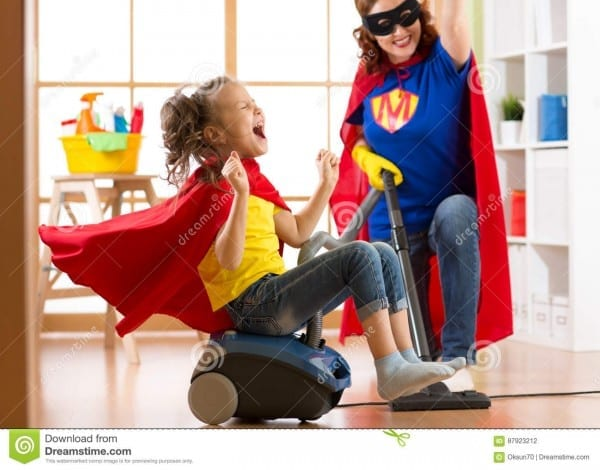 Child And Mother Dressed As Superheroes Using Vacuum Cleaner In