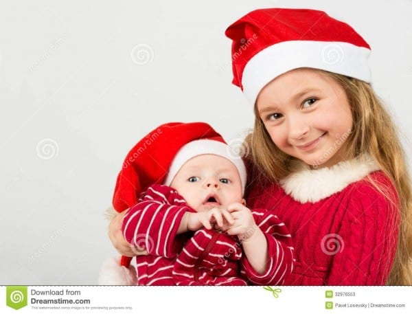 Girl Stand In Santa Claus Hats And Holding Baby Boy Stock Image