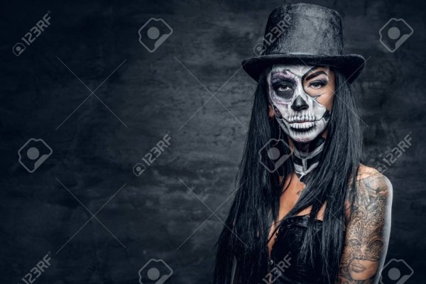 Portrait Of Female With Skull Make Up In Top Hat On Halloween