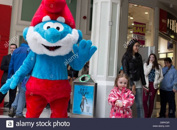 A Person Wearing A Papa Smurf Costume Stands Beside A Little Girl