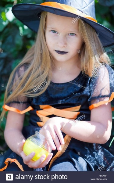 Portrait Of Cute Little Girl Wearing Witch Costume With Broom On