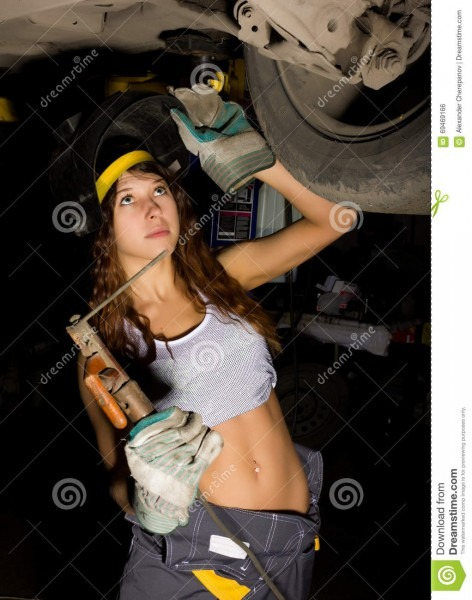 Beautiful Young Female Mechanic Inspecting Car In Auto Repair Shop