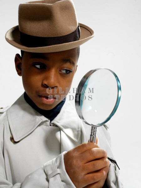 Child Wearing Detective Costume Holding Magnifying Glass Stock