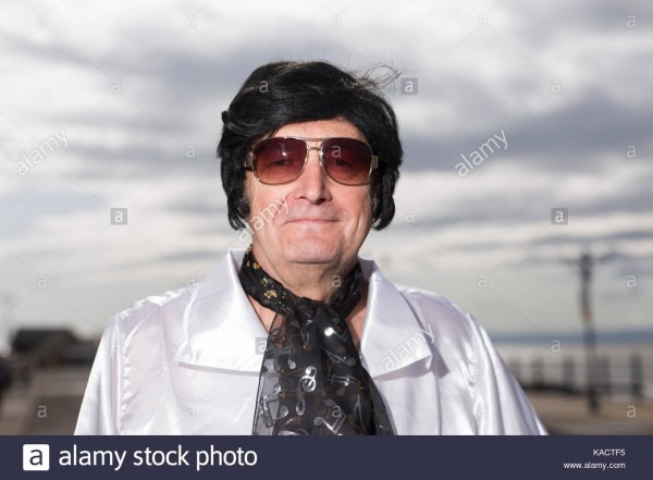 Man In White Elvis Costume And Black Wig Smiles, Sky For