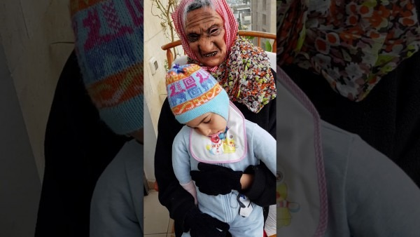 Nofar In Illusion Costume Of An Old Woman Holding A Baby