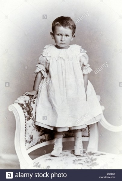 Studio Portrait Of Victorian Child With Short Hair Wearing A Smock