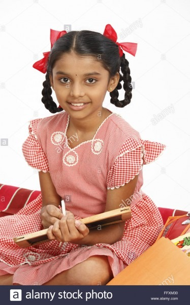 Ten Years Old Girl Writing On Slate With Chalk Sitting On Charpoy