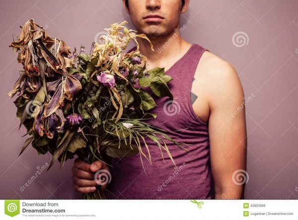 Young Man Holding Bouquet Of Dead Flowers Stock Image
