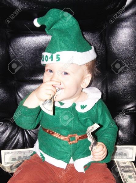 Cute Little Baby Boy In Green Santa Suit Eats Dollar Bills Stock