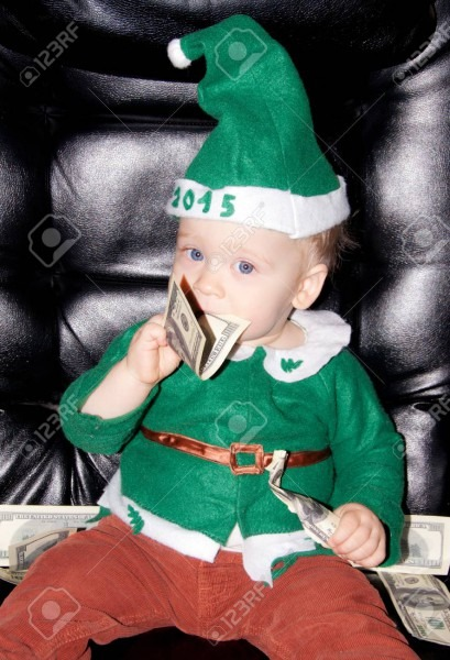 Little Baby Boy In Green Santa Suit And Hat Eats Present Dollars