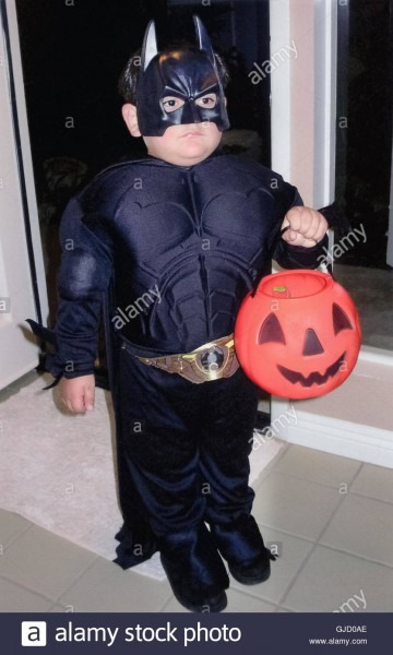 A Serious Young Boy In A Batman Costume Holds A Plastic Orange