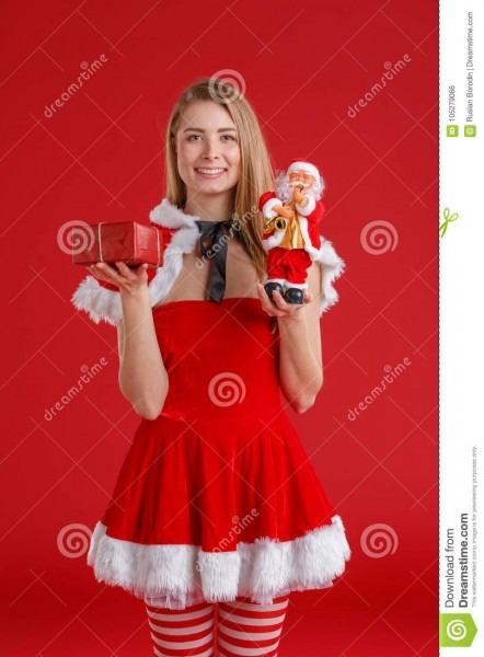 A Young Girl In A Elf Dress And Stockings, Holds A Red Gift Box, A