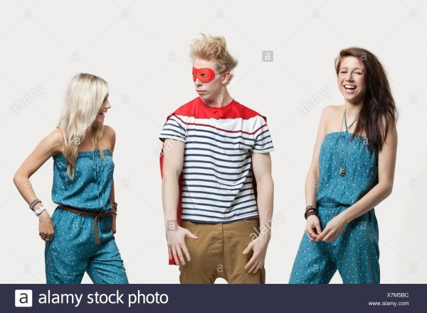 Young Man In Superhero Costume Standing With Happy Female Friends