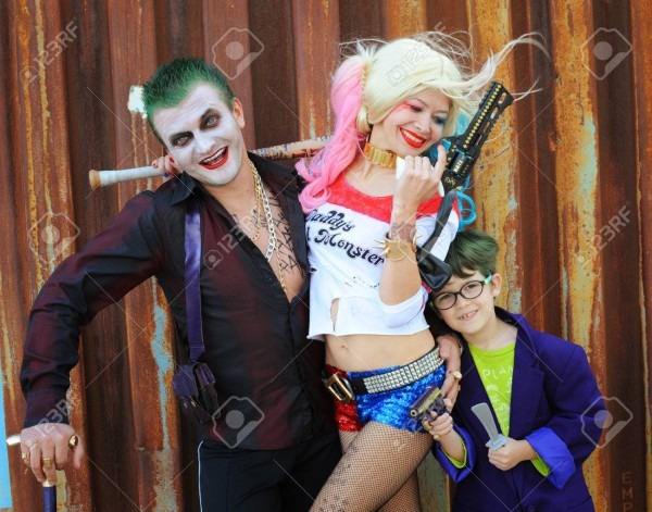 Cosplayer Girl In Harley Quinn Costume And Cosplayer Men In Joker