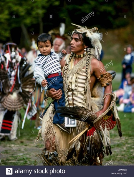 A Native American Indian Father Dressed In Tribal Costume Dancing