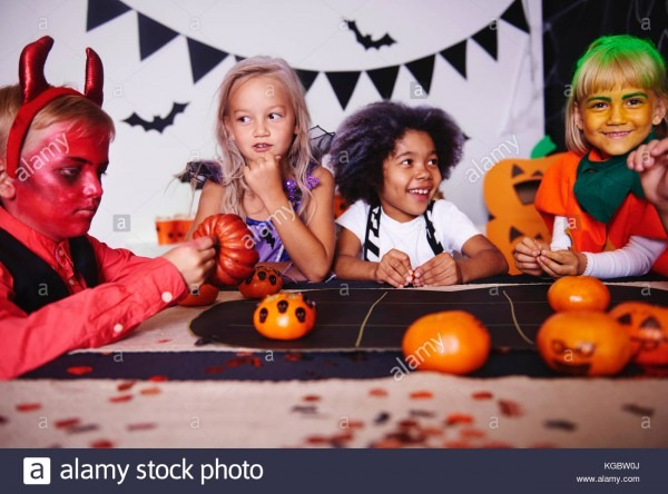 Children Playing In Costume At Halloween Party Stock Photo
