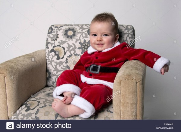 9 Month Old Baby Boy Wearing A Santa Suit, Grinning And Sitting On