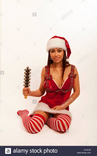 Asian Woman In A Santa Outfit Playing Jingle Bells Stock Photo
