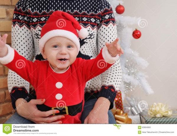Happy Cute Little Baby Boy In Santa Suit Sitting On Mother's Kne