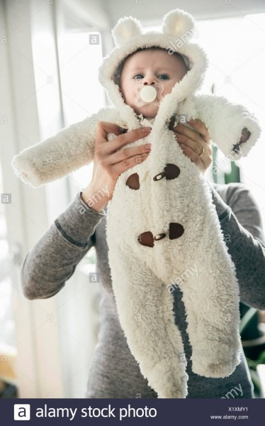 Mother Holding Up Baby In A Polar Bear Costume Stock Photo