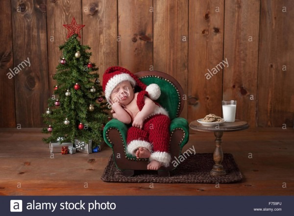 Newborn, Baby Boy Wearing A Santa Suit And Sleeping On A Tiny